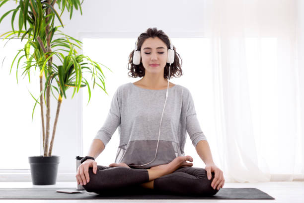 Modern woman with headphones sitting in yoga lotus posture Slender female folded crossed legs in lotus position. Young athletic woman in fitness tracker and headphones is practicing yoga, meditating, relaxing while sitting in padma asana at home. zen stock pictures, royalty-free photos & images