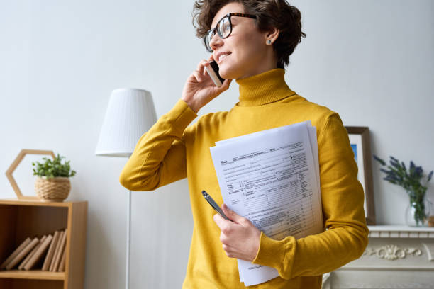 Moderne Frau mit Steuerpapieren telefoniert – Foto