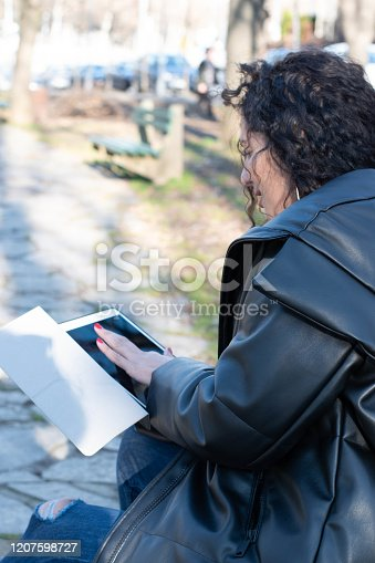 855341616istockphoto Modern woman working at park using tablet or Ipad 1207598727