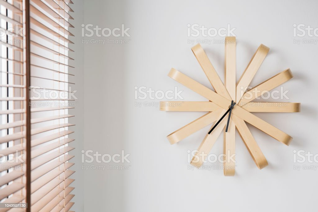 Modern Wooden Clock On White Wall Next To Window With Blinds In