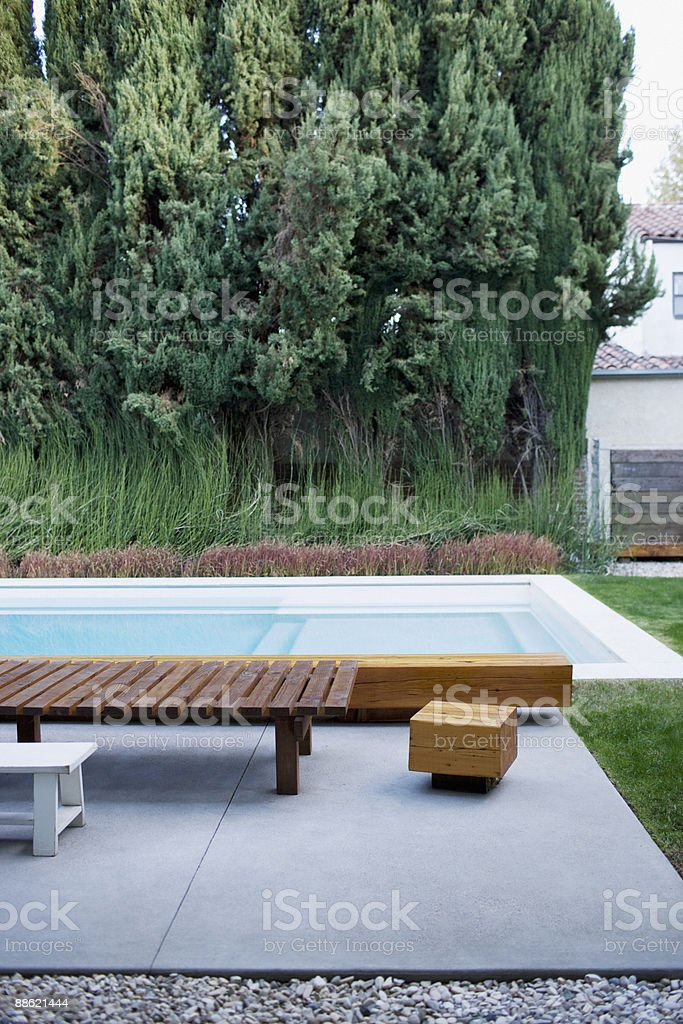 Modern wooden lounge chair next to swimming pool royalty-free stock photo