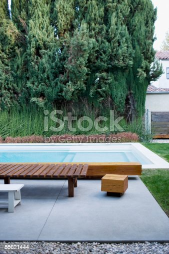 Modern Wooden Lounge Chair Next To Swimming Pool Stock Photo & More Pictures of Bench
