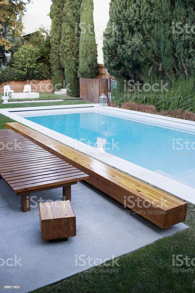 Moderne en bois, une chaise longue à côté de la piscine photo libre de droits