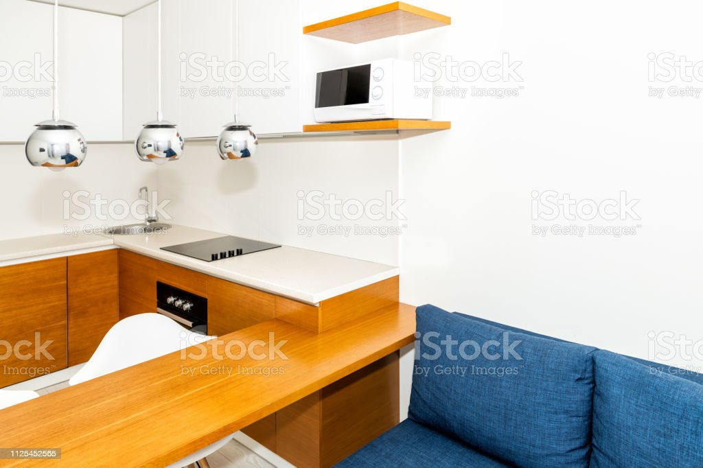 Modern Wooden Orange Kitchen Features Cabinets In Small Apartment Studio Bar Stool Counter Interior Design And Nobody On Blue Sofa In Minimalist Home Stock Photo Download Image Now Istock