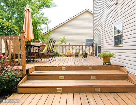 istock Modern wooden patio and garden area of a family house 469109748