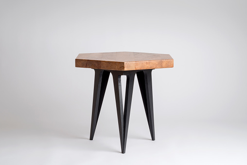 Modern wooden stool or small table with hexagonal top and black painted legs isolated on white background