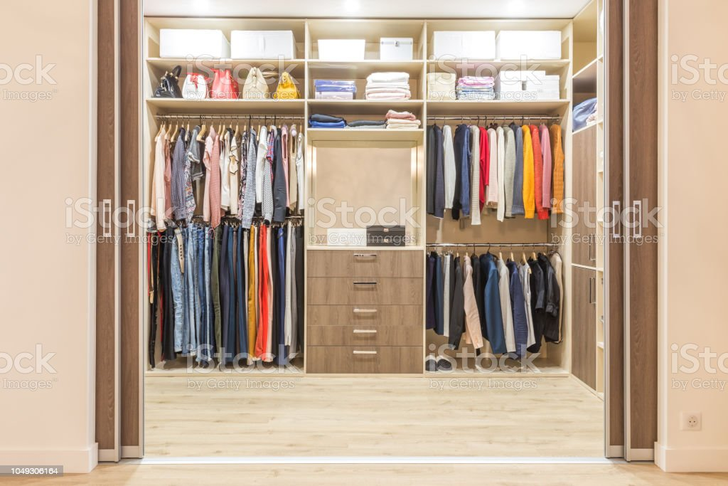 Modern wooden wardrobe with clothes hanging on rail in walk in closet stock photo