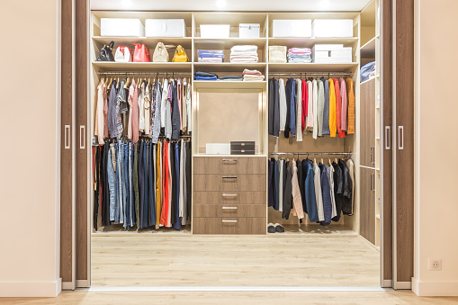 Modern Wooden Wardrobe With Clothes Hanging On Rail In Walk In Closet Stock Photo - Download Image Now