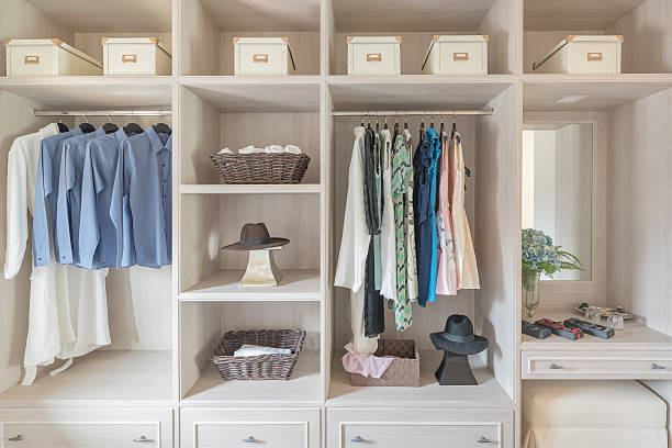 modern wooden wardrobe with clothes hanging on rail - closet stock photos and pictures