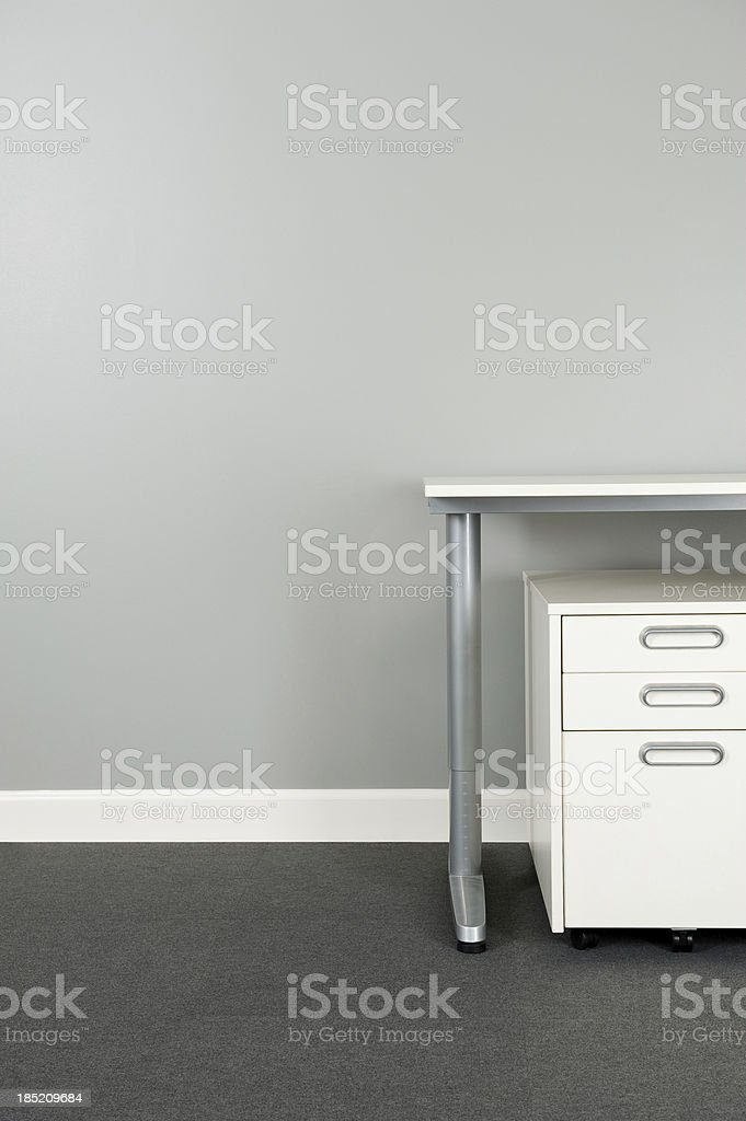 Desk and file cabinet in empty modern office. The carpeting is made...