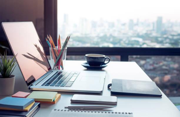 近代的な仕事テーブル ウィンドウからコンピューターのラップトップと都市景観ビュー。ビジネス概念のアイデア - 机 ストックフォトと画像