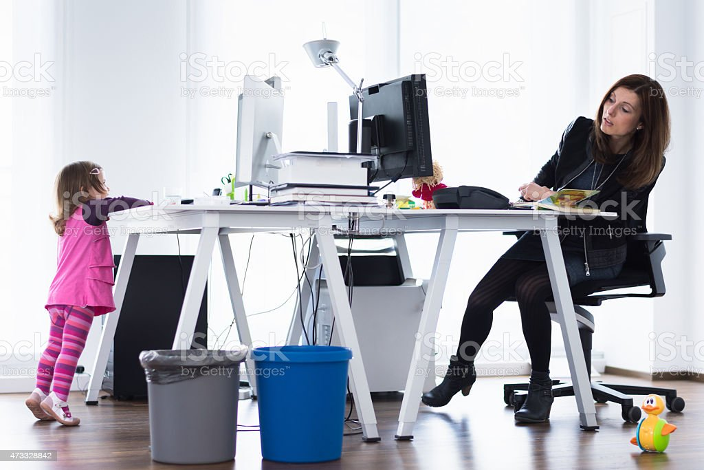 Modern working mother watching little daughter playing in the office stock photo