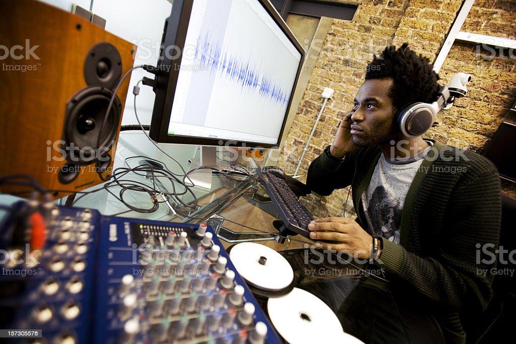 modern workplace: audio engineer working in his studio editing samples stock photo