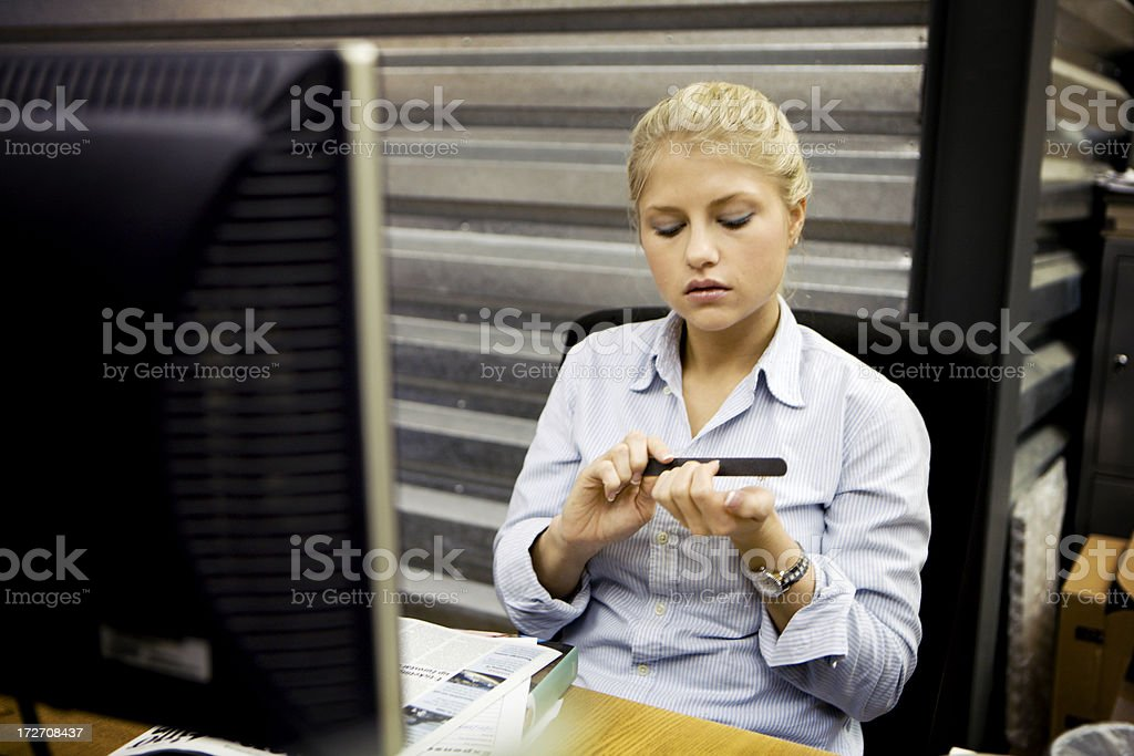modern workplace: bored office worker filing her nails royalty-free stock photo