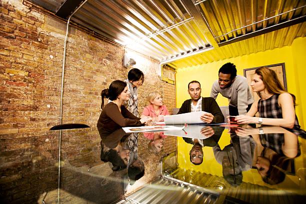 modern workplace: candid office meeting in a contemporary board room - projektledning bildbanksfoton och bilder