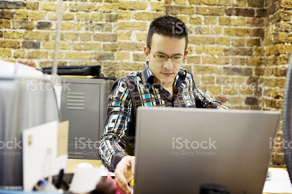 modern workplace: contemporary creative professional concentrating on his computer royalty-free stock photo