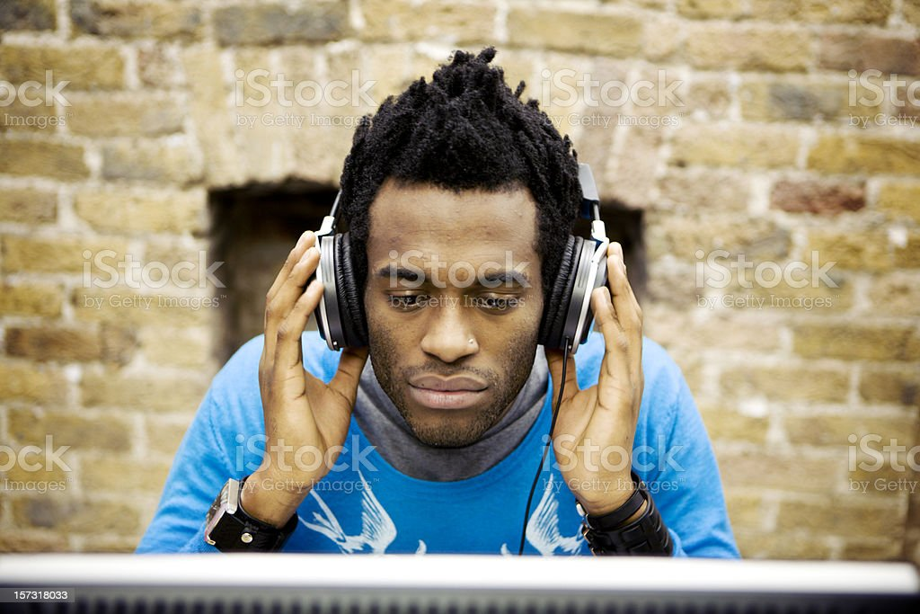 modern workplace: creative professional listening to music through his headphones stock photo