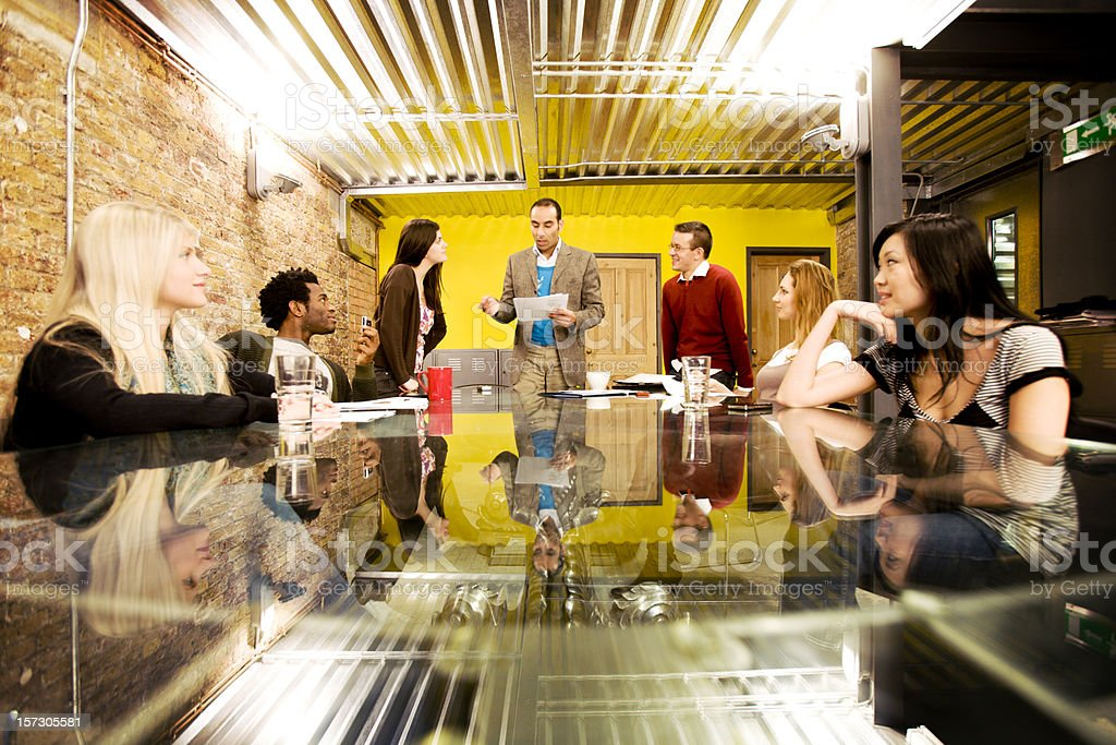 modern workplace: meeting of creative professionals listening to their manager stock photo