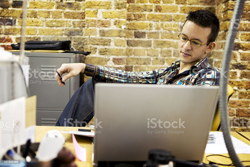 modern workplace: relaxed office professional candidly working at his desk royalty-free stock photo