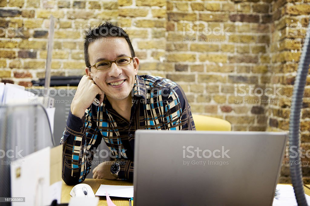 modern workplace: relaxed office professional sitting smiling at his desk stock photo