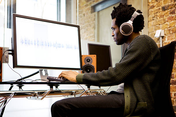 modern workplace: sound editor at his desk editing wave forms stock photo