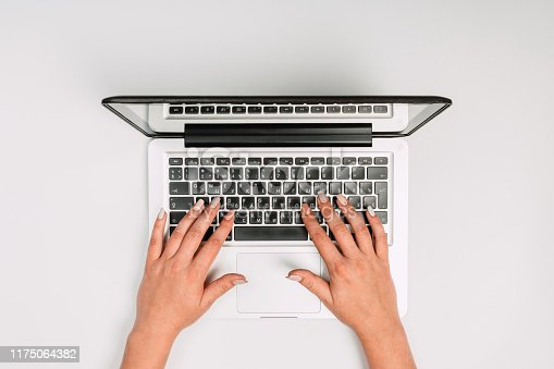 1173922060 istock photo Modern workspace with woman hands and laptop copy space on white color background. Top view. Flat lay style. 1175064382