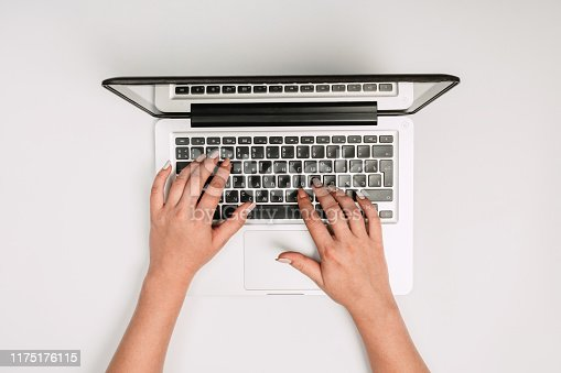 1173922060 istock photo Modern workspace with woman hands and laptop copy space on white color background. Top view. Flat lay style. 1175176115