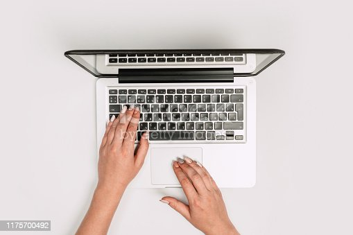 1173922060 istock photo Modern workspace with woman hands and laptop copy space on white color background. Top view. Flat lay style. 1175700492