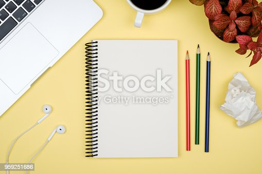istock Modern yellow office desk table with laptop and blank notebook page for input the text. Top view, flat lay 959251686