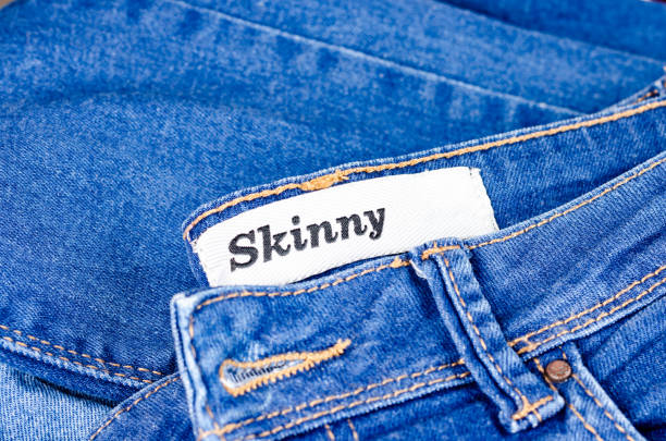 Modern young blue jeans denim with tag skinny for lean people . Women and Men fashion accessory .Top view, copyspace. Modern young blue jeans denim with tag skinny for lean people . Women and Men fashion accessory .Top view, copyspace. skinny jeans stock pictures, royalty-free photos & images