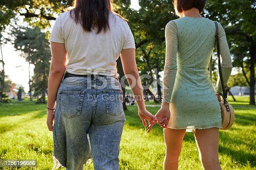 Beautiful and young homosexual lesbian couple in love, enjoying a sunny day together at a park.