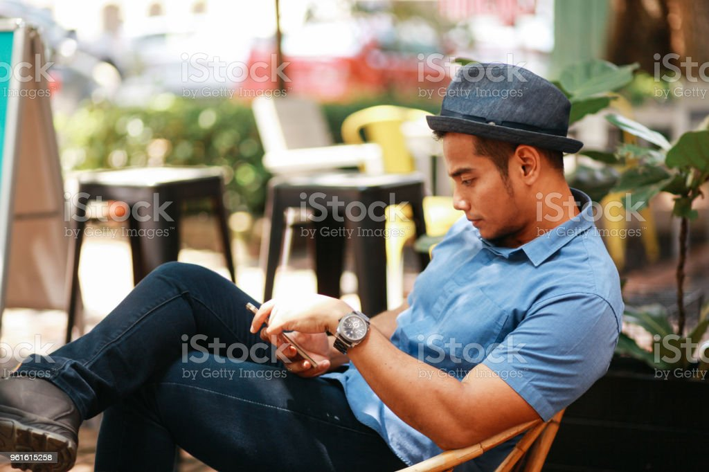46711fdcb14 Modern Young Man Texting On The Cellphone On The Streets Of Kuala ...