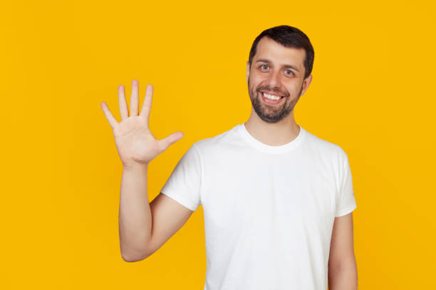 Modern young man with a beard in a white tank top shows number five with fingers on hand, smiling confidently and happily, looking at the camera The man shows five fingers. Number 5. yellow background stock photo