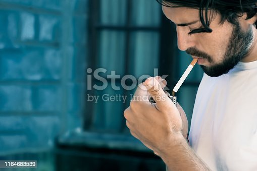 Modern young man with beard he lights a cigarette, toning