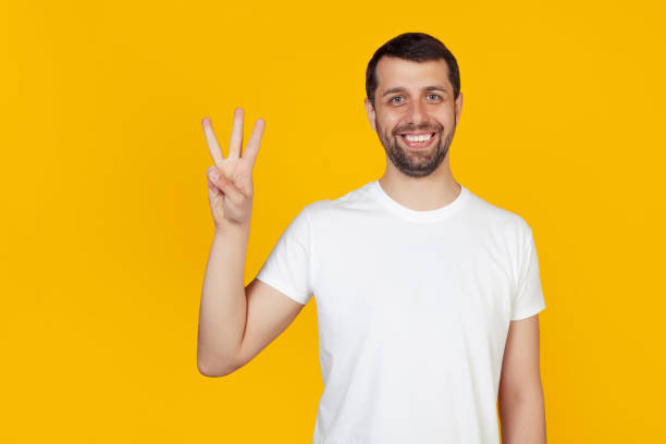Modern young man with beard in white t-shirt showing with fingers number three, smiling confidently and happy, looking at the camera. Number 3. yellow background stock photo