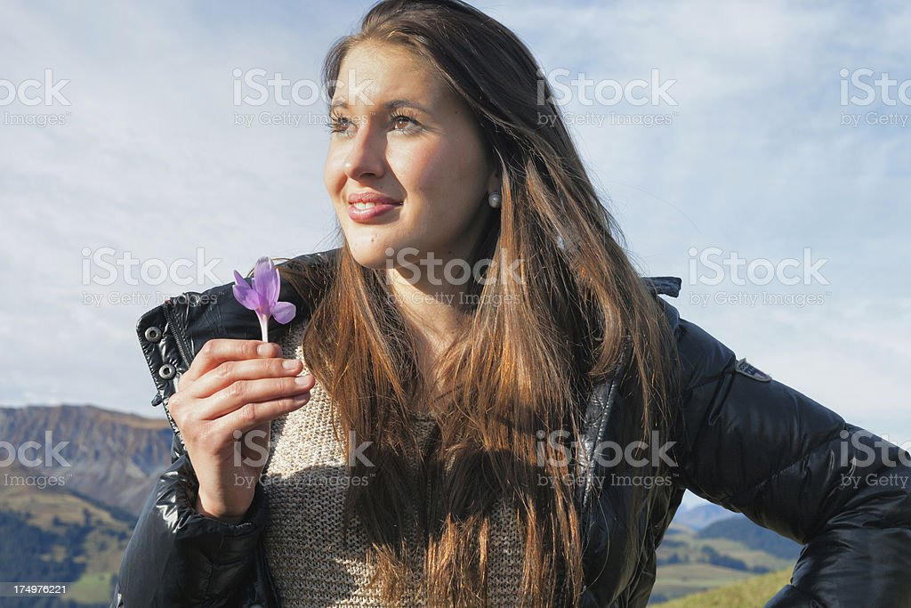 Modern Young Woman holding alpine flower Swiss Alps royalty-free stock photo