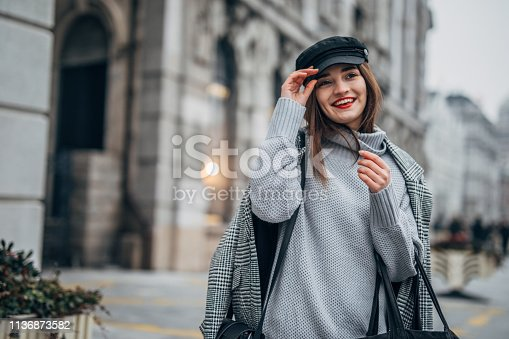 518885222istockphoto Modern young woman with hat 1136873582