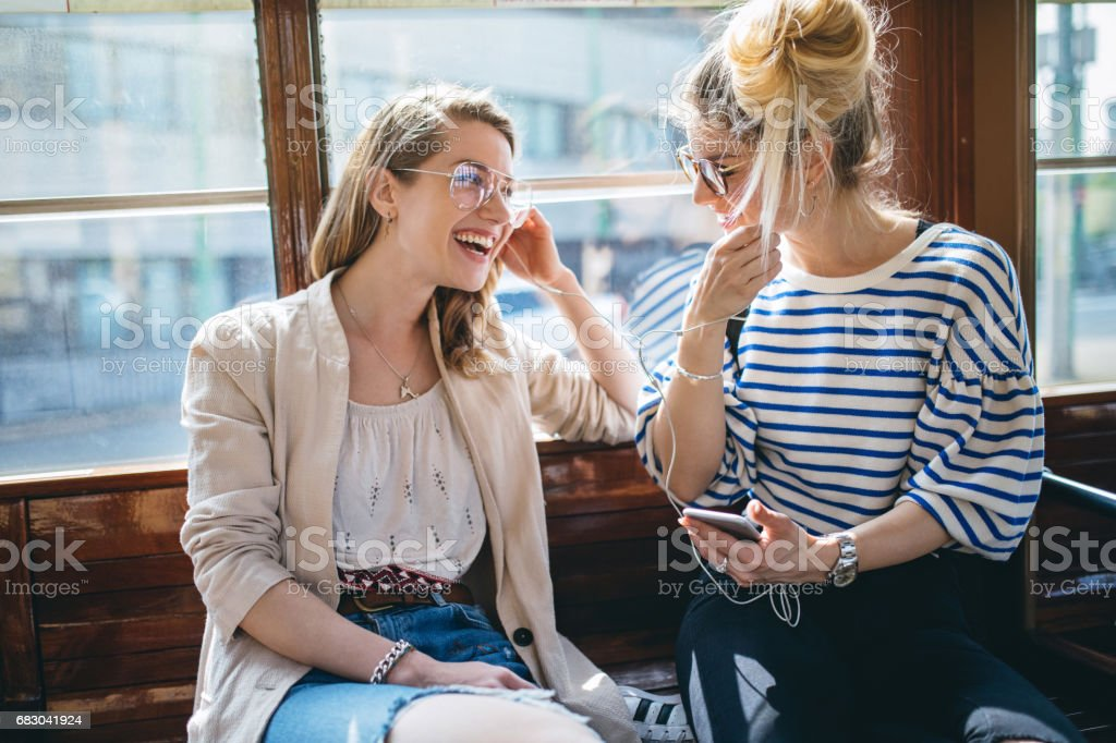 Modern young women listening to music in city transportation stock photo