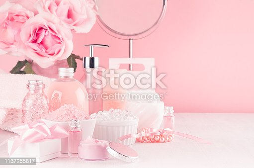 1056636898 istock photo Modern youth bathroom or dressing table design in pastel pink color -  flowers, cosmetic products, bath accessories, jewelry, round mirror on white wood board. 1137255617