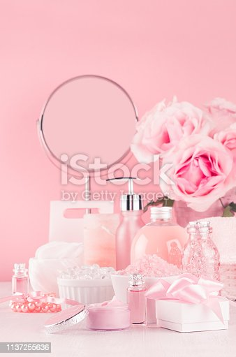 1056636898istockphoto Modern youth bathroom or dressing table design in pastel pink color - fresh pink flowers, cosmetic products, bath accessories, jewelry, round mirror on white wood board. 1137255636
