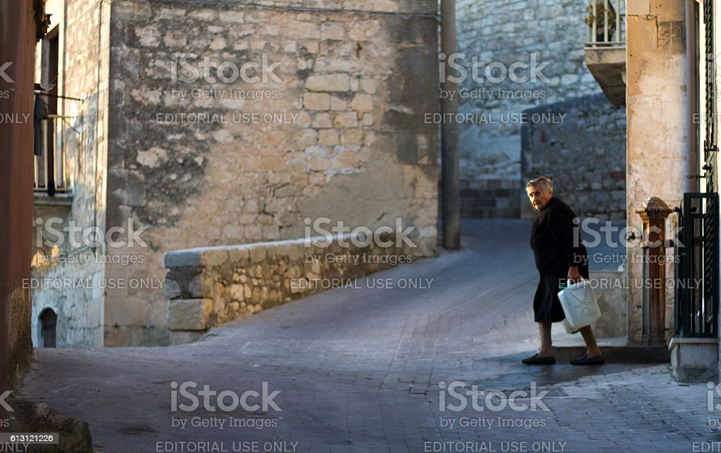 Modica, Sicily: Senior Woman in Black Hauling  Well Water
