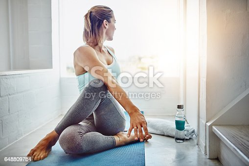 Shot of an attractive woman practising her yoga routine at home