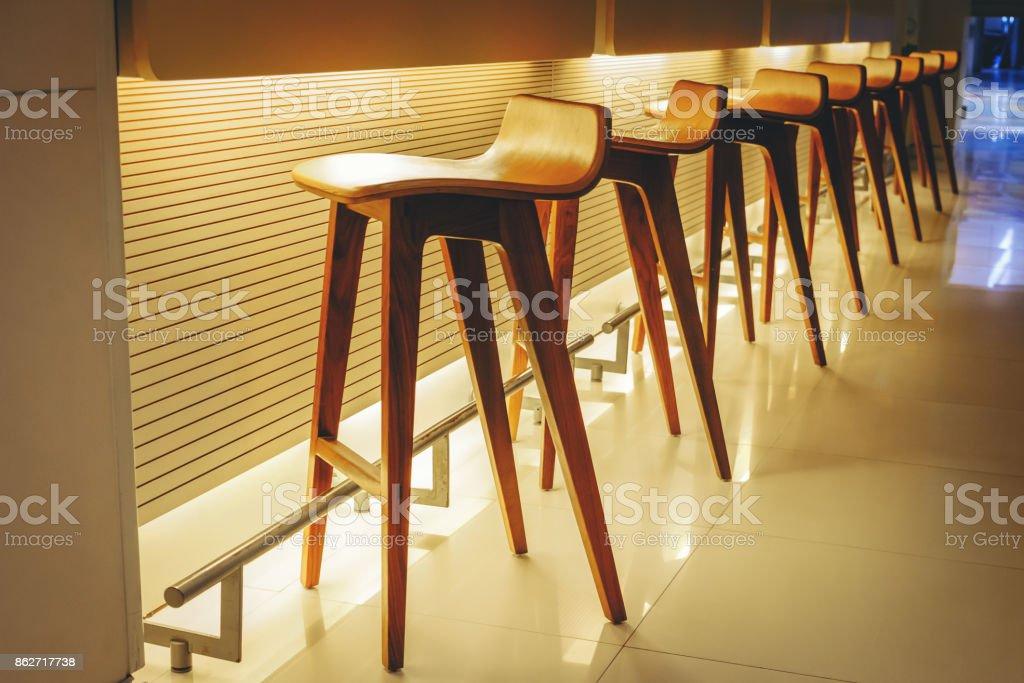Modren Zeile leer Holzstühle, innere Hintergrund legen braune hölzerne Hochstühle in der Nähe der Bar oder Theke – Foto