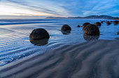 Dawn breaks over some of the mysterious Moeraki Boulders on New Zealand's South Island.