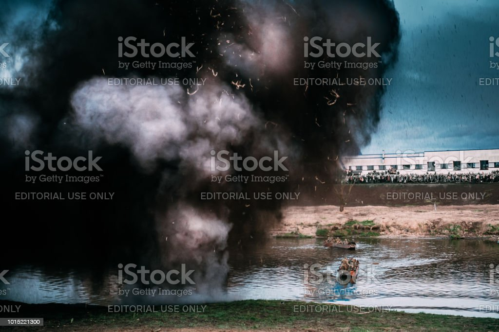Mogilev, Belarus. Reenactors Dressed As Russian Soviet Red Army Infantry Soldiers Of World War II Make Crossing Of River On A Boat. Artillery Shelling, Bombardment Of Landing Site On River Bank stock photo