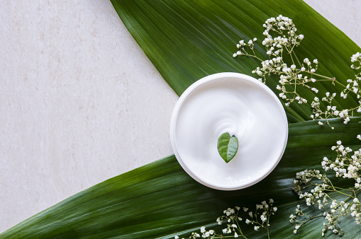 Top view of cosmetic lotion with white flowers and green leaf. Skin care beauty treatment with jar of body moisturizer. High angle view of white body lotion with little green leaf on marble background.