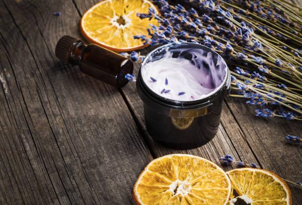 vochtinbrengende crème biologisch met een lavendel en oranje droog op een houten tafel - creme huid stockfoto's en -beelden