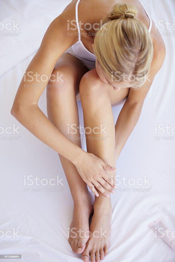 Moisturizing her legs stock photo