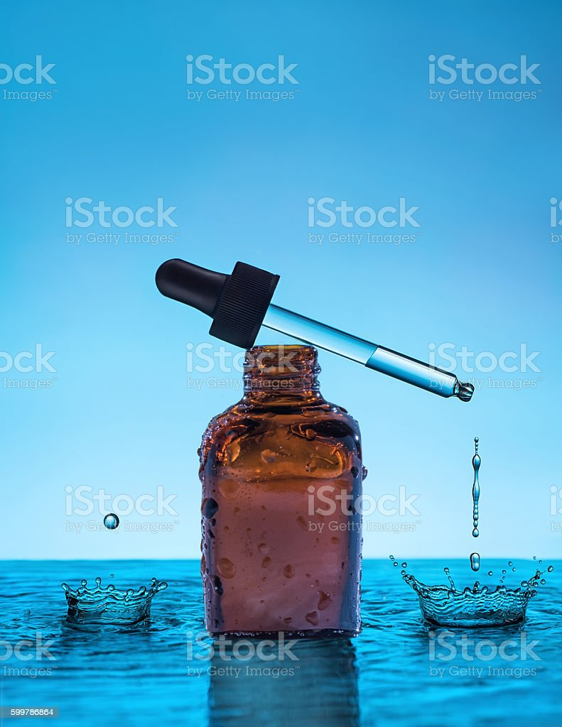 Moisturizing serum for dry skin stands in the water stock photo