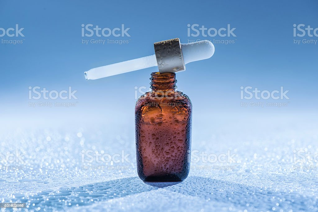 Moisturizing  serum on the blue  background with  water drops stock photo